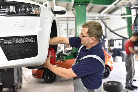 car mechanic in the workshop changes the brakes of the vehicle