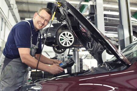 smiling car mechanic in a workshop - engine repair and diagnosis on a vehicle