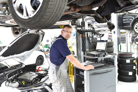 car mechanic maintains a vehicle with the help of a diagnostic computer - modern technology in the car repair shop Reklamní fotografie