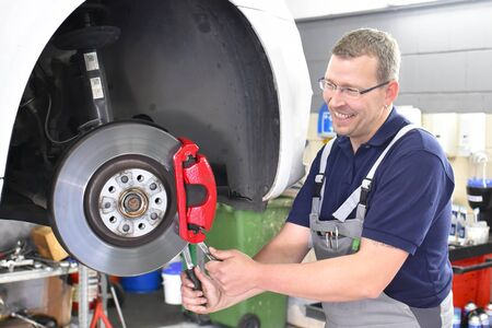 car mechanic repairs brakes of a vehicle on the lifting platform in a workshop