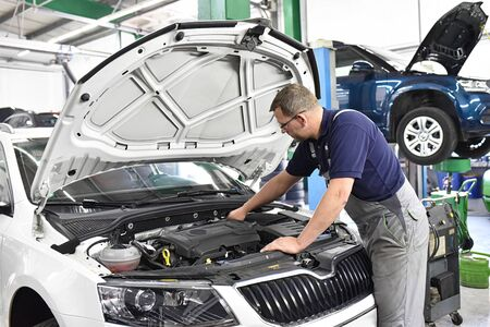 car mechanic checks the engine of a vehicle - in the background car on the lifting platform - workplace and profession