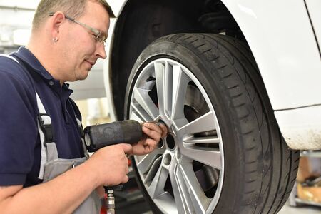 Car mechanic changes the tires of the vehicle in the workshop Reklamní fotografie