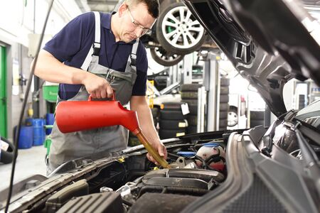 Engine oil change from the car by a mechanic in the car workshop