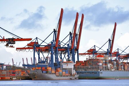 transport and logistics by water - loading of ships in a port with goods for export Stock Photo