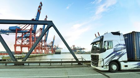 transport and traffic - trucks on the road and a terminal with ships in the background