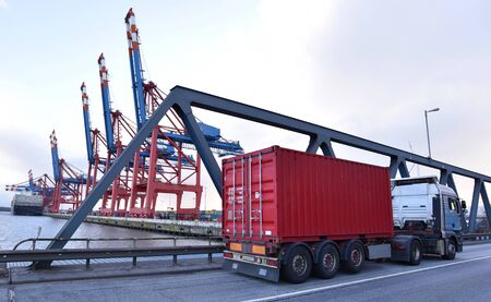 transport and traffic - trucks on the road and a terminal with ships in the background Reklamní fotografie
