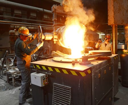 workers in a foundry casting a metal workpiece - safety at work and teamwork