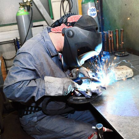 welder at a workplace in metal construction working on a workpiece made of metal  Zdjęcie Seryjne