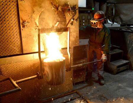 workers in a foundry casting a metal workpiece - safety at work and teamwork Фото со стока