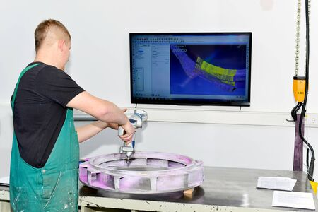 quality control - workers at a measuring station to check the dimensions of a machine component
