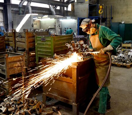 workers in safety clothing sanding a casting in an industrial company