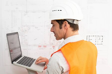 Architect at his workplace with notebook - house building and construction in industry Stockfoto