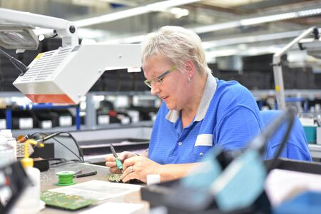 friendly woman working in a microelectronics manufacturing factory - component assembly and soldering Banque d'images