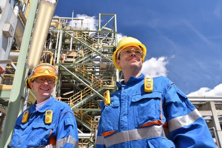 Group of industrial workers in a refinery - oil processing equipment and machinery 免版税图像