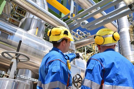 group of industrial workers in a refinery - oil processing equipment and machinery Foto de archivo