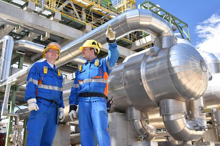 Teamwork: group of industrial workers in a refinery - oil processing equipment and machinery 免版税图像