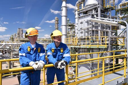 Teamwork: group of industrial workers in a refinery - oil processing equipment and machinery Reklamní fotografie