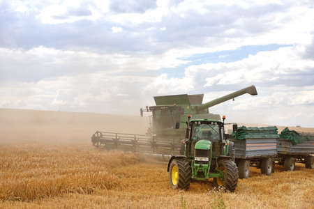 combine harvester and tractor in the cereal field during the summer harvest