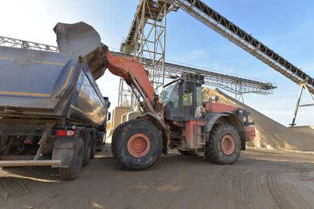 Gravel pit: building and wheel loader loading gravel onto a truck Reklamní fotografie - 151436004