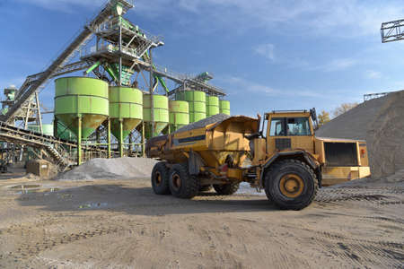 Gravel pit: building and wheel loader loading gravel onto a truck