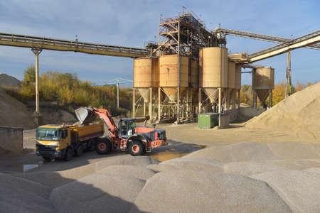 Gravel pit: building and wheel loader loading gravel onto a truck Reklamní fotografie - 151436571