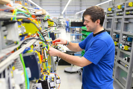 young apprentice assembles components and cables in a factory in a switch cabinet - workplace industry with future Reklamní fotografie - 155020264