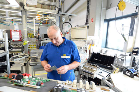 older friendly worker in an industrial company assembles electronic components in the mechanical engineering of a modern factory Reklamní fotografie - 155020716
