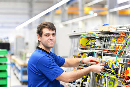 young operator assembles machine in a modern high tech factory - production of switch cabinets for industrial plant