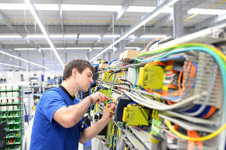 young apprentice assembles components and cables in a factory in a switch cabinet - workplace industry with future Reklamní fotografie - 155020149
