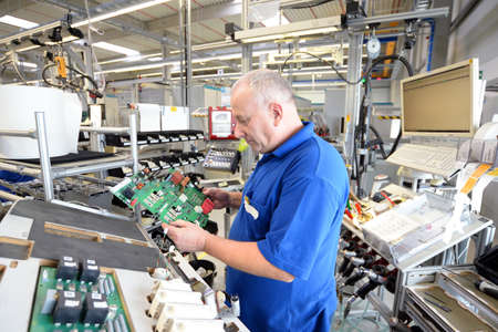 older friendly worker in an industrial company assembles electronic components in the mechanical engineering of a modern factory