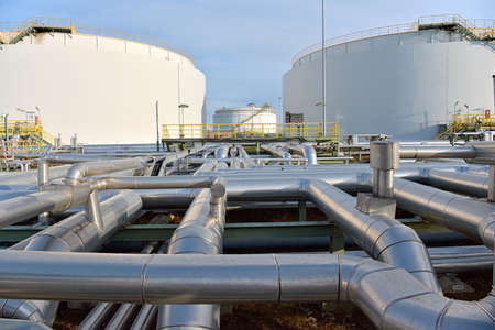 pipeline, storage tanks and buildings of a refinery - industrial plant for fuel production Reklamní fotografie - 155878011