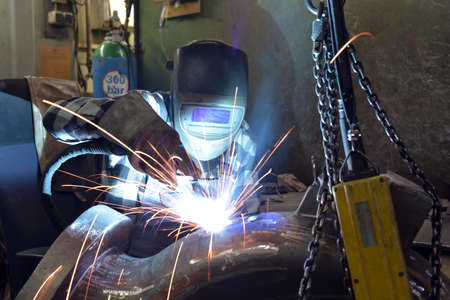 Welder in protective clothing at the workplace in an industrial company in steel construction Reklamní fotografie - 157027174