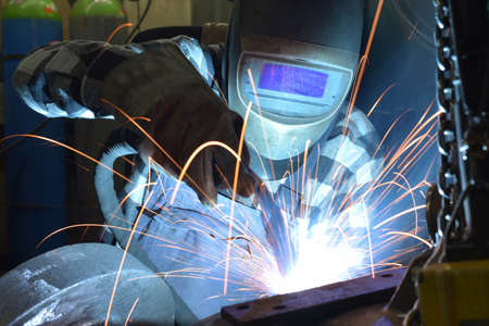 Welder in protective clothing at the workplace in an industrial company in steel construction