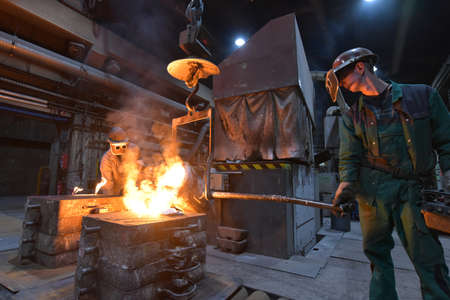 workers in a foundry casting a metal workpiece - safety at work and teamwork Reklamní fotografie - 157026109