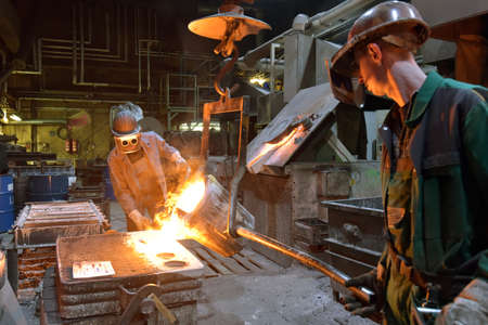 workers in a foundry casting a metal workpiece - safety at work and teamwork Reklamní fotografie - 157026482