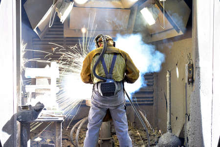 Welder in protective clothing at the workplace in an industrial company in steel construction Reklamní fotografie - 157079257
