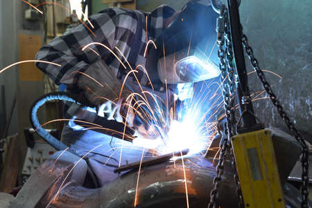 Welder in protective clothing at the workplace in an industrial company in steel construction Banque d'images
