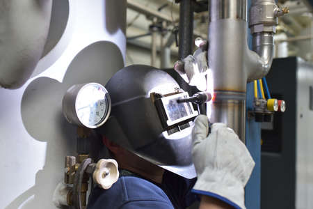 welder works in steel construction and repairs an industrial plant