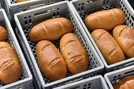 Storage and transport of freshly baked loaves of bread in a bakery for sale - industrial food production Stock fotó