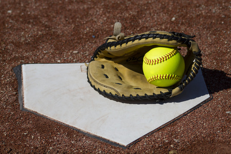 catcher's mitt: A Fastpitch Catchers Mitt With Yellow Ball On Homeplate