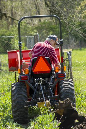 Older Farmer Watching His Plow On The Back Of His Compact Tractor