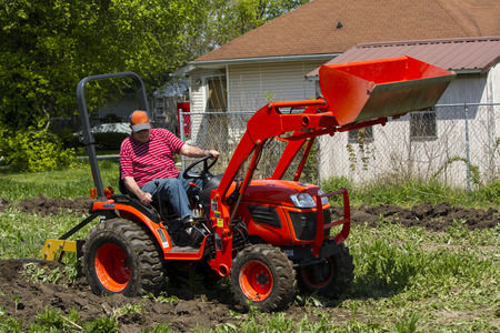 Older Farmer Using His Compact Tractor To Plow A Garden Patch