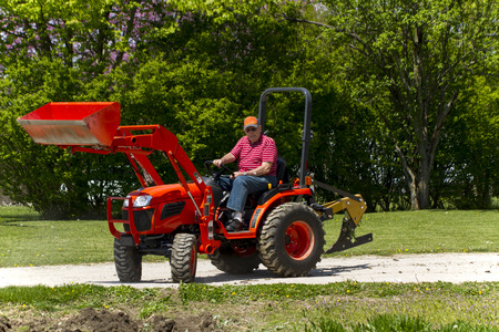 compact: Older Man Getting Ready To Plow A Small Garden On His Compact Tractor Stock Photo