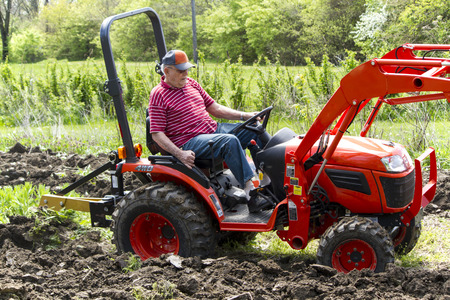 Elderly Man Plowing His Garden With A Compact 4x4 Tractor