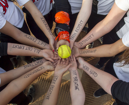 homeplate: Girls Fastpitch Softball Team Inspirational Huddle Stock Photo
