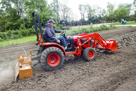 Older Farmer Stirring Up The Dust While Tilling His Garden With A 4x4 Compact Tractor Archivio Fotografico