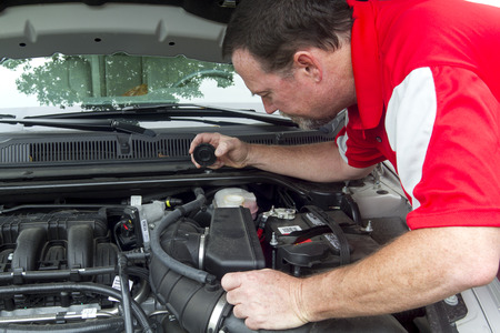 A Mechanic checking a master cylinder and the brake fluis levels. Stock Photo