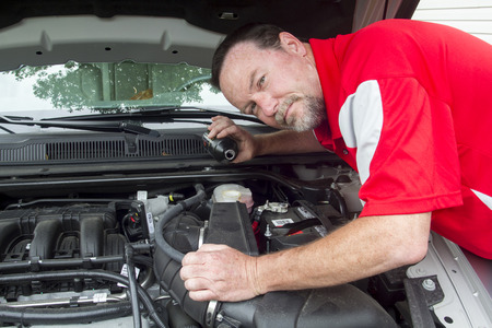 A mechanic putting brake fluid in a customers car. Stock Photo
