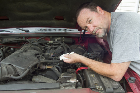 viscosity: A mechanic checking oil levels in a older vehicle.