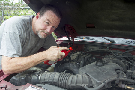 viscosity: A mechanic adding oil to a older truck. Stock Photo